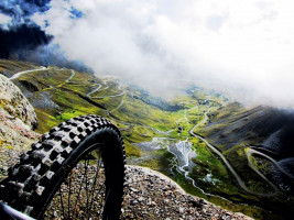 mountain bike wheel at edge of drop looking down at the Death Road, Bolivia