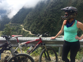 Woman with mountain biking helmet standing next to mountain bikes with Death Road, Bolivia in the background